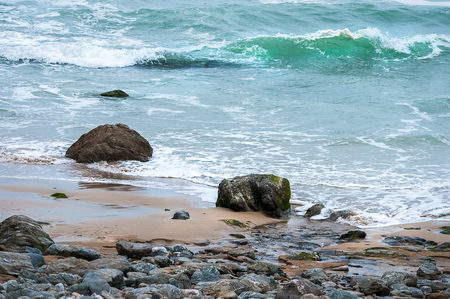 Rocks, pebbles and sand with sea waves at Chapel Porth in Cornwall.