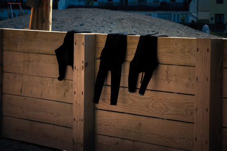 Three black wetsuits drying on a wooden fence at the end of the day. Stock Photo
