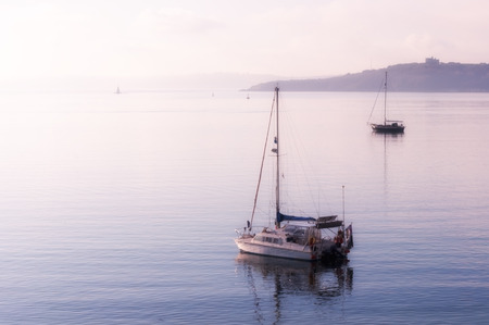 High-key image of yachts moored in calm sea at St Mawes in Cornwall as the morning mist lifts.