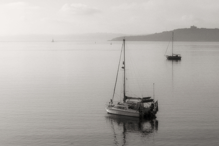 High-key monochrome image of yachts moored in calm sea at St Mawes in Cornwall as the morning mist lifts. Stock Photo