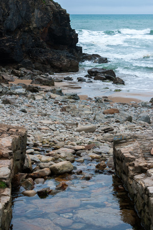 Stream running into the sea through rocks and pebbles at Chapel Porth beach, St Agnes, Cornwall. Stock Photo