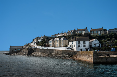 View across Porthleven harbour entrance to the Ship Inn and the old lifeboat house.