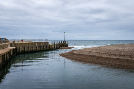 Narrow channel and sandbank where River Axe enters the sea at Axmouth harbour. Stock Photo