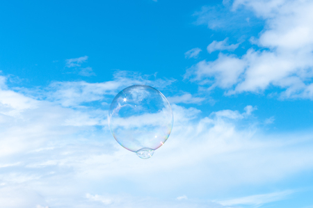 Large bubble floating up into a clear blue summer sky with fluffy white clouds.