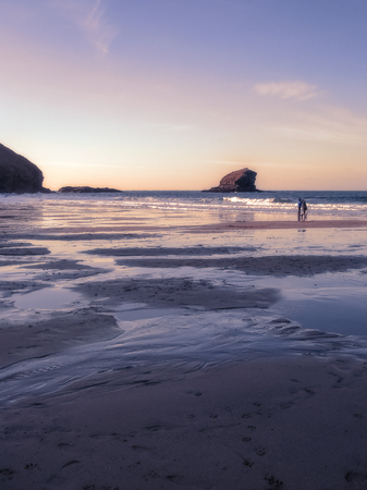 View across the sands to Gull Rock, Portreath, Cornwall, as the sun sets beyond the cliff.