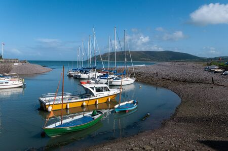 Boats at Porlock Weir, Somerset,  with Bossingon Hill beyond. Stock Photo