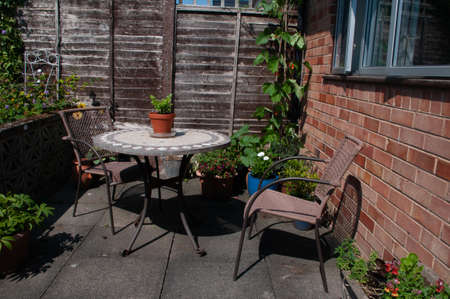 Runner beans, courgette or zucchini and celery growing on garden pation in containers by table and chairs.