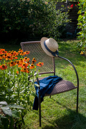 Summer boater style straw hat with blue ribbon on garden chair outdoors with blue jacket or cardigan, sunny summer day, heleniums in foreground, runner beans behind. Stock Photo