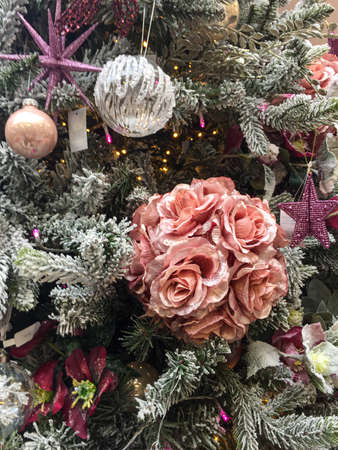 Decorations on Christmas tree including pink roses, stars and baubles.