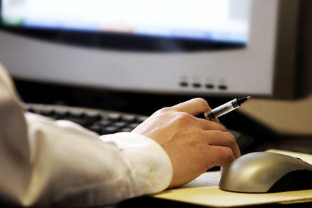 raton: La celebraci�n de l�piz a mano delante de la pantalla del ordenador, con el rat�n y el teclado - representa el ordenador de trabajo y la investigaci�n.