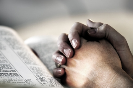 prayer: Mans hands clasped in prayer over a Holy Bible - represents faith and spirituality in everyday life.
