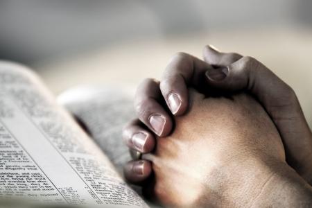 Man's manos abrochadas en rezo sobre una Santa Biblia - representa la fe y la espiritualidad en la vida cotidiana.  Foto de archivo - 336280