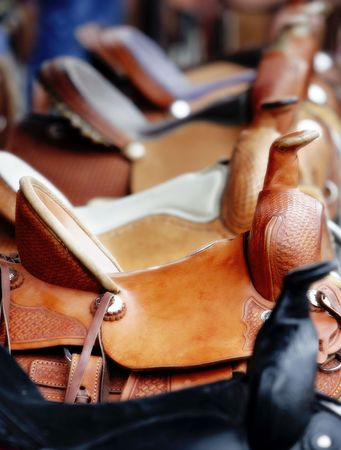 A Line of Western Saddles for Sale (shallow focus). photo