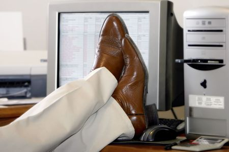 project deadline: Business man puts his feet up on his desk after success or ignoring work to be done (shallow focus). Stock Photo