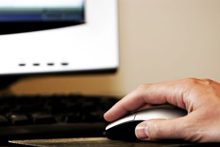 webmaster website: Hand using a mouse in front of a computer (shallow focus).