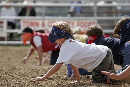 friendly competition: Blindfolded children race on hands and knees at a charity Watermelon Crawl in small town, rural America (shallow focus).