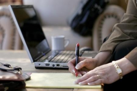 Escribir notas de negocios junto a su ordenador portátil en un hotel atrio (someras punto de enfoque a mano con pluma)  Foto de archivo - 415362
