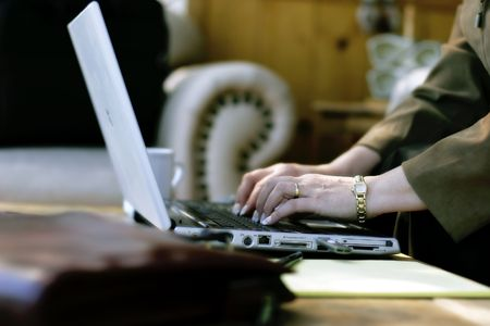 Businesswoman working at laptop computer in a hotel atrium (shallow focus point on foreground hand).