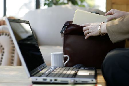 Businesswoman pulling a file from briefcase next to her laptop computer in a hotel atrium (focus point on foreground hand). Stock Photo