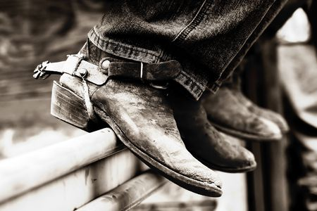 Rodeo cowboys' experienced boots & spurs on an iron rail (shallow focus, high contrast black & white effect)