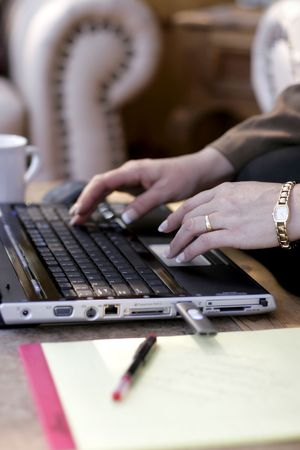 Close-up of businesswoman typing on a laptop computer in a hotel lobby (shallow focus point on foreground hand).