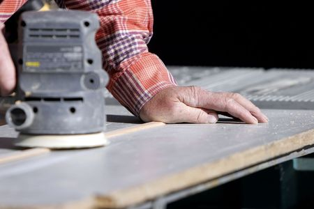 experienced: Experienced construction workers hands and a power sander (shallow focus).