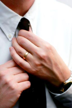 straighten: Married Hands Straighten a Necktie