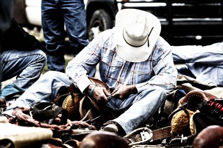 work boots: Rodeo cowboy working on his gear behind the scenes. Stock Photo