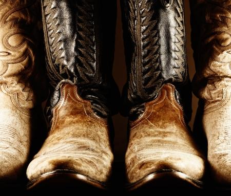 botas vaqueras: Botas de vaquero viejas en luz de alto contraste Foto de archivo