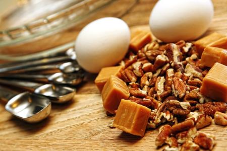 Ingredientes y utensilios que se utilizan en hornear un postre dulce y de nuez se extienden sobre una superficie de madera y listo para funcionar. Poca profundidad de campo. Foto de archivo - 58294845