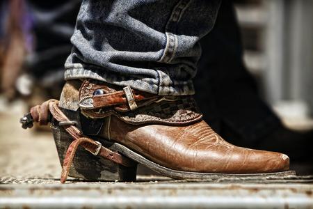 Cierre para arriba de la bota de un vaquero del rodeo y estimular, mientras se prepara detrás de las rampas para un próximo viaje. Foto de archivo - 58446292