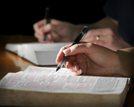 The hands of a couple are highlighted as they study the Holy Bible together - focus point on the womans foreground hand.