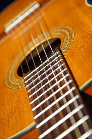 A close up photo of the neck and body of a six string classical guitar (also known as a Spanish guitar).  The strings are nylon versus the steel strings typically used in acoustic guitars.  Shallow depth of field. Stock Photo