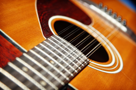 A close up of the neck and body of an acoustic twelve-string guitar - shallow depth of field. Stock Photo