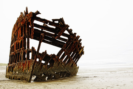 The rusted frame of the Peter Iredale rests wrecked in heavy fog on the northwest Oregon coast. The sailing vessel was a four-masted steel barque that ran aground in 1906 and is now a tourist spot. Stock Photo