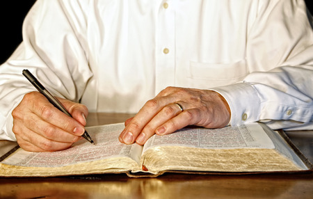 A businessman or business executive in a white, long-sleeved shirt takes time out of his day to study the Holy Bible. Stock Photo