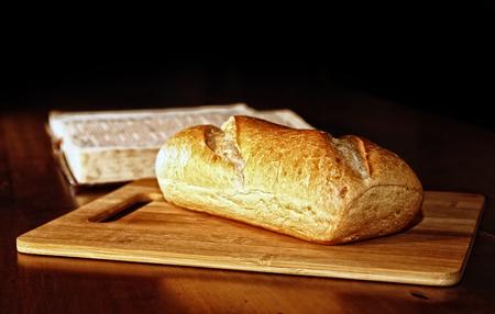 Nuestro Pan Diario - Un pan rústico de pan está en una tabla de cortar de madera delante de una Santa Biblia abierta en el fondo. Foto de archivo - 85932634