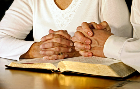 A married couple wearing white shirts clasp their hands in prayer together over an open Holy Bible.  Main focus point is on the womans hands.