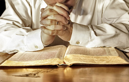 A married man in a white, long-sleeved shirt bows his head and has his hands clasped in deep prayer over his Holy Bible.