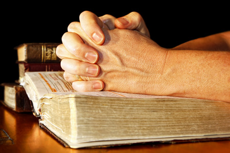 A man folds his hands in committed prayer over a Holy Bible, while light shines directly on his hands and the open bible. Stock Photo