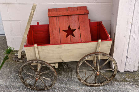 Vintage wooden toy wagon and a red wooden door with a star cut into it against a white-washed stone background.