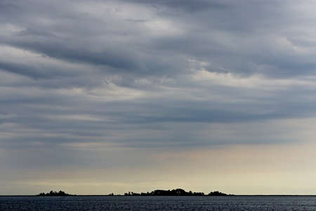 Dramatic, wind-swept clouds over small, uninhabited islands in the Chesapeake Bay.