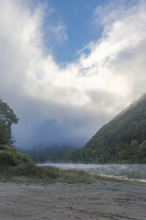 Kittatinny Point, Pennsylvania: Sun shines through the mist over the Delaware River on a early morning in the Delaware Water Gap.
