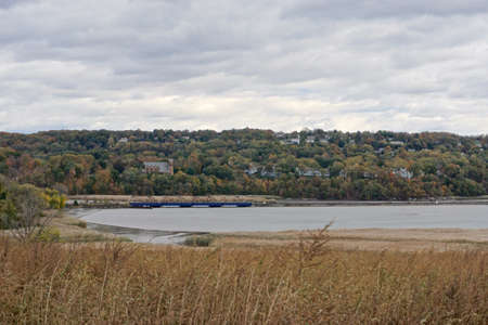 Westchester, NY: A rail bridge spans an inlet on the Hudson River, with St. Augustines Roman Catholic Church, Ossining, NY, in the background.