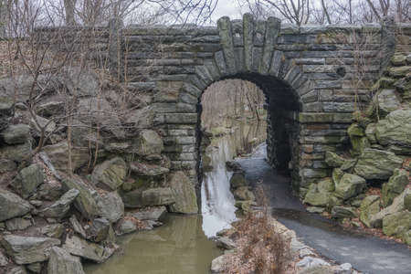 New York, New York: A stream flows under the Glen Span Arch, in the northwest section of Central Park, on a cloudy day.