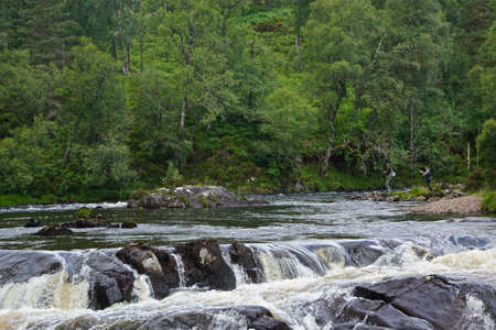 Glen Affric National Nature Reserve, Scotland, UK: Two men fishing on the River Affric in Glen Affric, described as the most beautiful in Scotland.