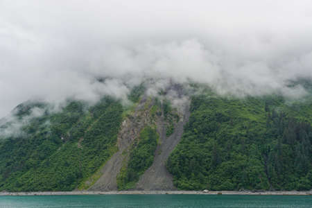 Yakutat Bay, Alaska, USA: Clouds descending on a mountainside at the edge of the bright green waters of Yakutat Bay.