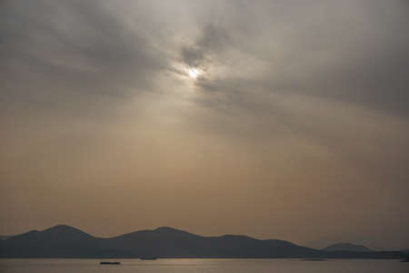 Piraeus, Greece: Sunset over islands in the Saronic Gulf (Gulf of Aegina) reveals a large amount of dust pollution in the atmosphere.