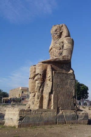 Luxor, Egypt: One of the Colossi of Memnon (1350 BC), two massive statues of the Pharaoh Amenhotep III, who reigned during the 13th Dynasty.