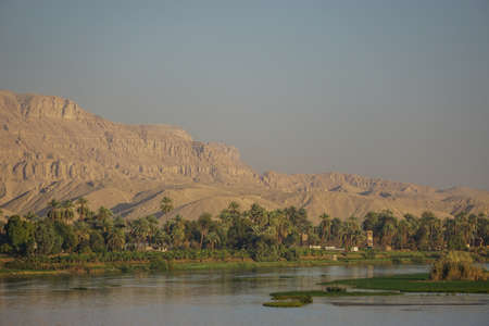 Nile River, Egypt: Houses and date palm trees along the west bank of the Nile; large sand dunes in the background; marshy islands in the foreground.